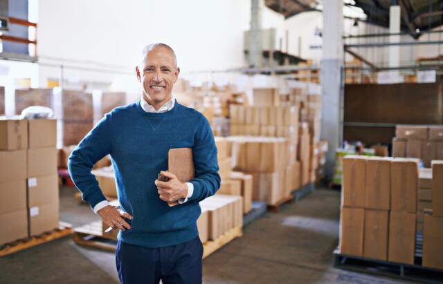 Man standing in warehouse with clipboard