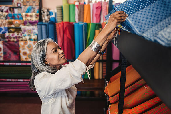 What is Multichannel Inventory Management ? Woman organizing inventory at fabric store