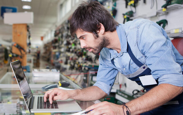 Man checking a mac laptop in a hardware store