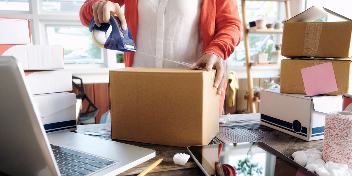 Woman packing ecommerce sales up for fulfillment with tape